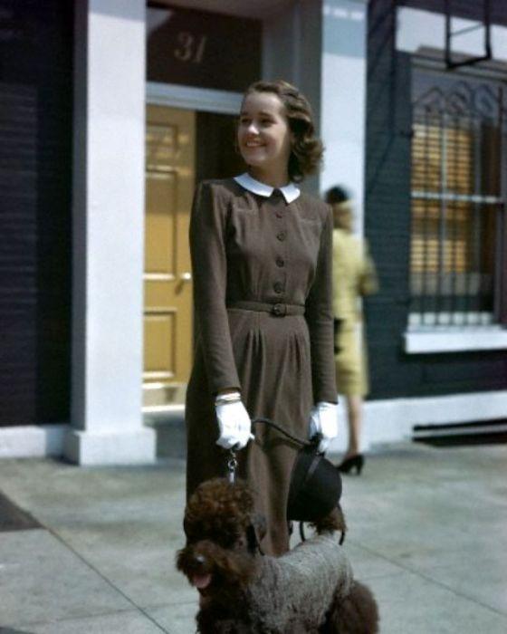 Модель позирует в мягком шерстяном платье с поясом и аккуратным белым воротничком, придающим образу элегантность.