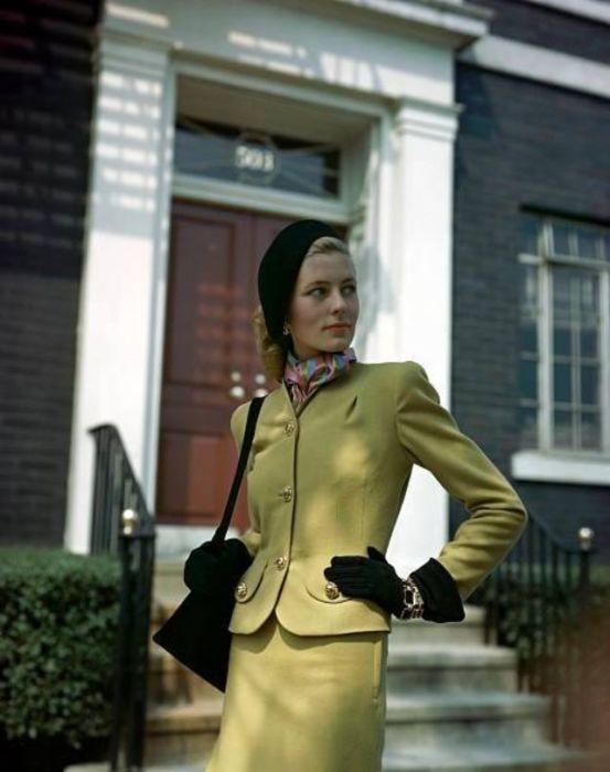 Девушка-модель в шерстяном костюме песочного цвета, декорированном большими золотыми пуговицами.