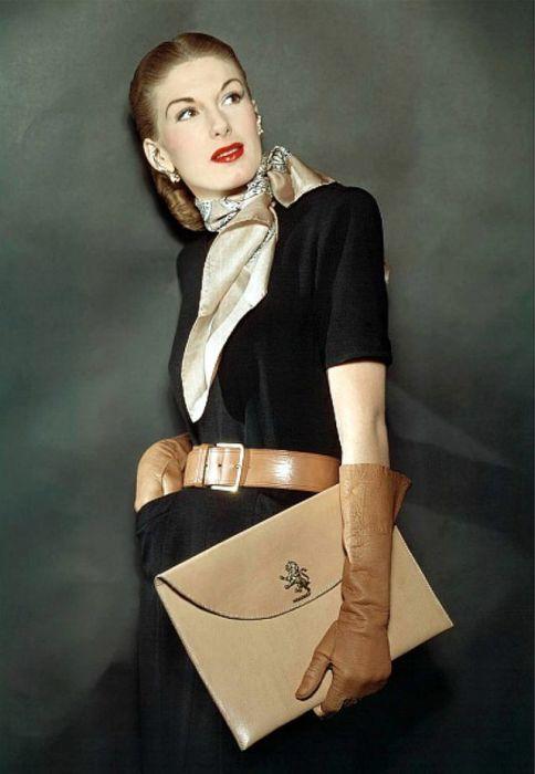 Модель в черном платье, дополненном аксессуарами сдержанных тонов для завершения стильного образа.