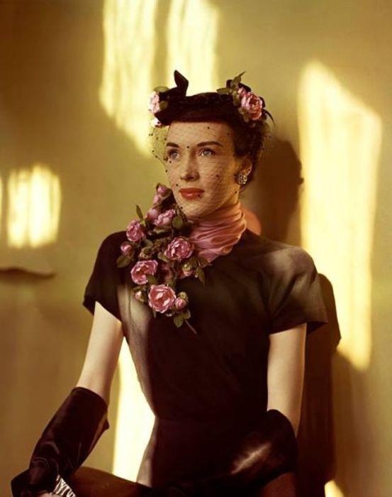 Образ модели состоит из черного платья с коротким рукавом, декорированной шляпки с вуалью и шелкового шарфа с розами.
