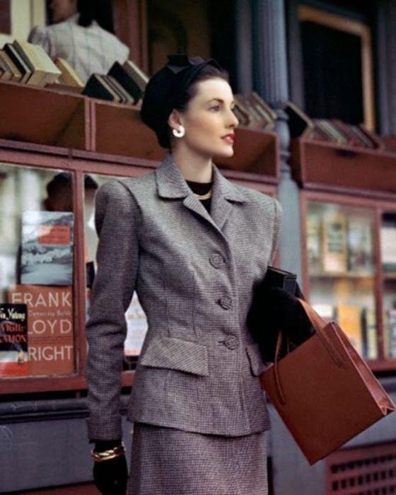 Модель в сером костюме позирует фотографу Константину Йоффе (Constantin Joffе) у нью-йоркского книжного магазина.