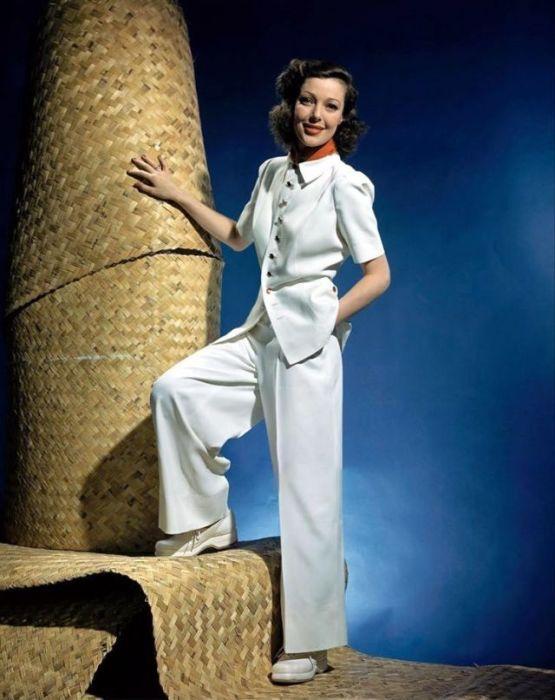 Американская актриса Лоретта Янг (Loretta Young) позирует на плетеной лестнице в брючном костюме белого цвета.