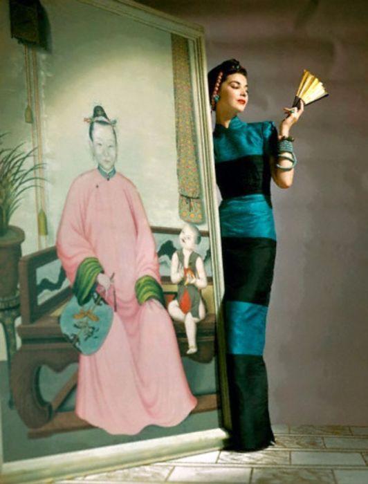 Модель позирует в длинном шелковом платье с черными вставками, которое идеально облегает фигуру.