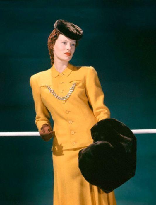 Девушка-модель в желто-золотом твидовом костюме, декорированном массивной цепочкой.