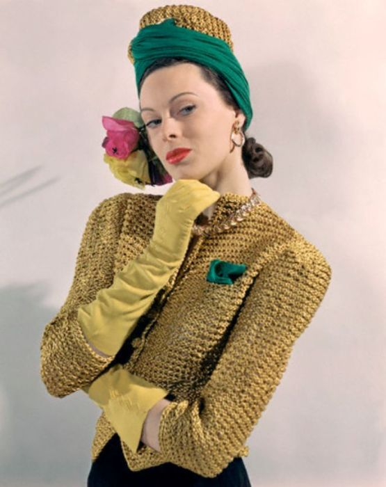 Модель в необычном головном уборе – золотом вязаном тюрбане, дополненным желто-розовыми цветами и зеленым платком.