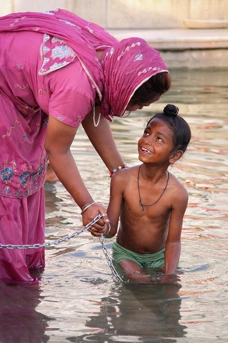 Мама купает сына в святых водах в Золотом храме Амритсара.