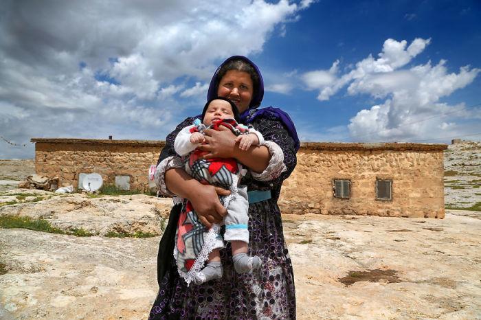 Мать позирует с маленьким сыном перед их домом возле Харрана.