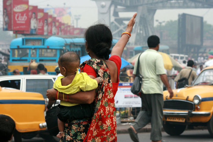 Мама с маленьким ребенком на руках пытается перейти улицу возле станции Хавра.