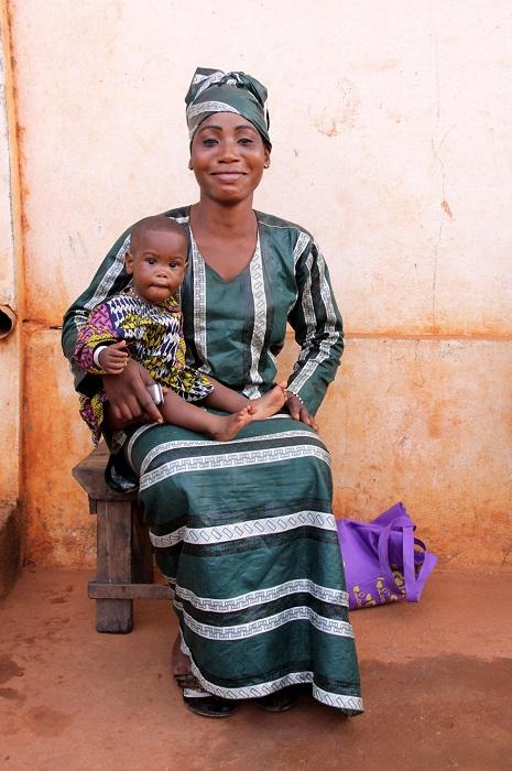 Мама в традиционной одежде позирует фотографу с сыном на руках.
