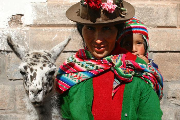 Мать в яркой одежде позирует вместе с сыном и альпакой на улице города, расположенного в Андах.