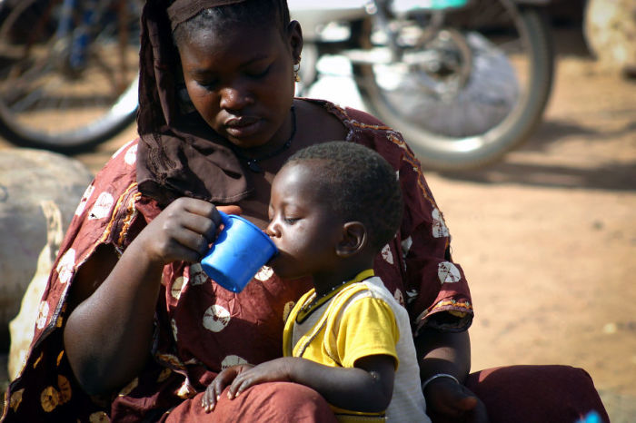 Мамочка, присевшая недалеко от городской толпы, чтобы напоить своего маленького сына.