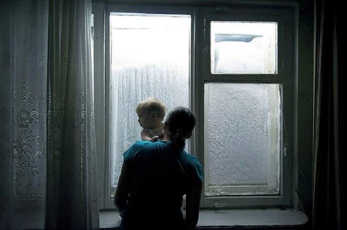 Женщина с маленьким ребенком рассматривает узоры на стекле.