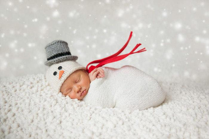 Новорожденный спит на мягеньком снегу.