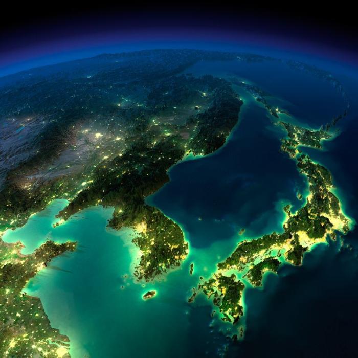 Под ясным небом горят ночные огни Кореи, Японии и Китая.