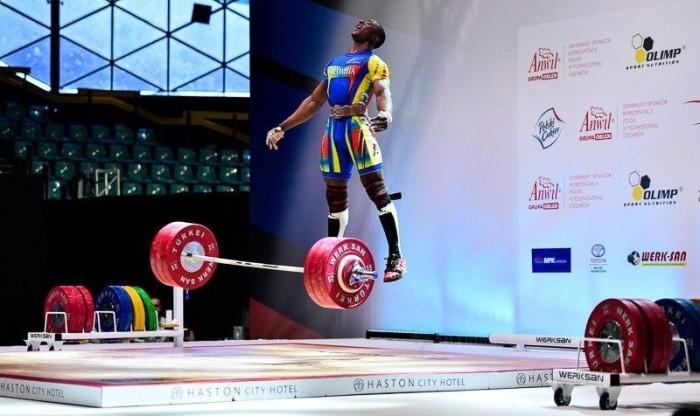 Удачный снимок спортсмена в прыжке, запечатлевший успешную попытку тяжеловеса поднять штангу весом в 190 килограмм.