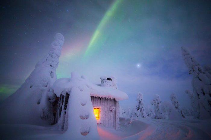 Километровая снеговая трасса для снегоходов и домик для отдыха замерли в ночных сумерках.
