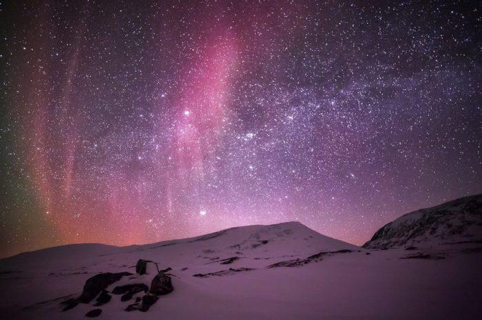 Мерцание красных, фиолетовых, зеленоватых цветов на звездном небе.