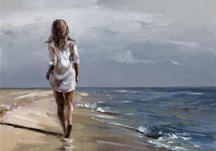 Девушка прогуливается по береговой линии моря.