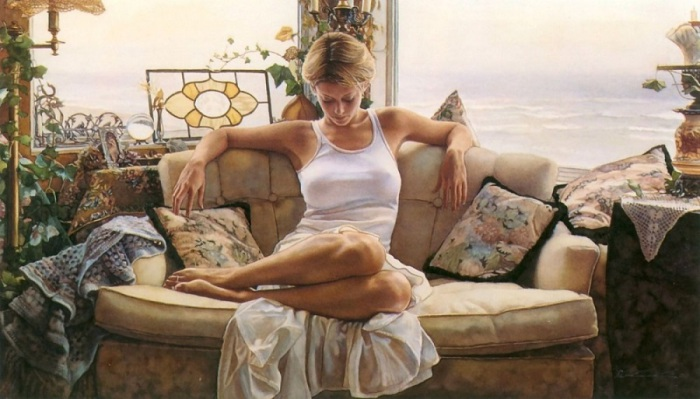Женщина в белой одежде и солнечных лучах отдыхает на диване.