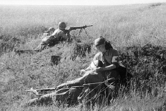 Медсестра оказывает первую помощь раненому во времена Великой Отечественной войны.