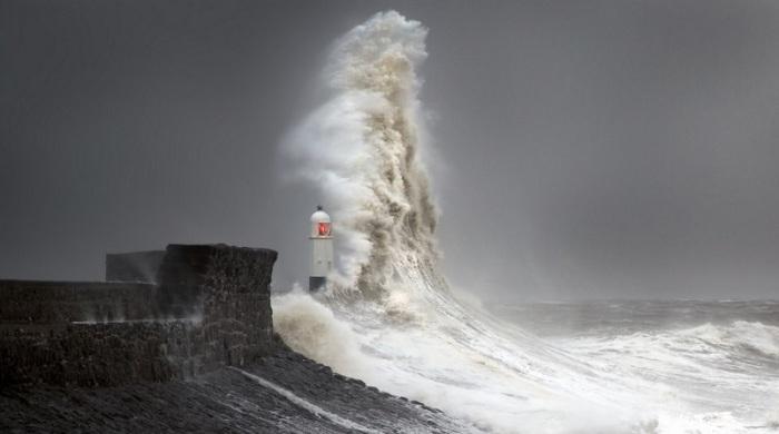 Волна своеобразно столкнулась с маяком и создала узкую вертикальную «стену» из брызг непосредственно перед строением.