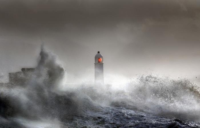 На этом снимке проход к маяку полностью поглотили разбушевавшиеся океанические волны.