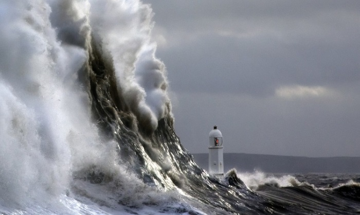 Темные океанские волны разбиваются о маяк и падают назад с грохотом и множеством белых брызг.