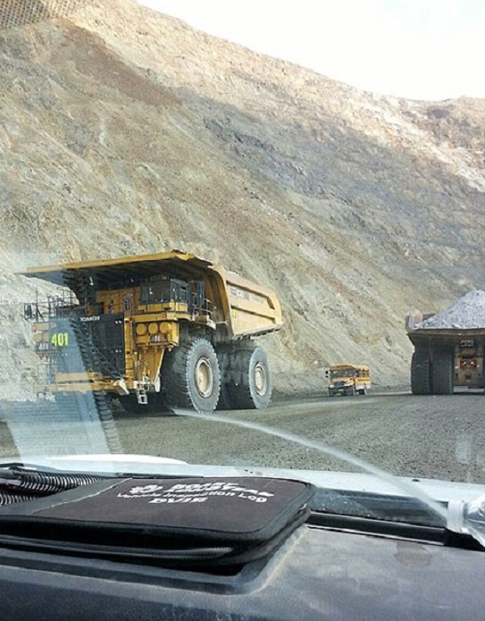 Школьный автобус выглядит карликом рядом с огромным мусоровозом, работающим на карьере.