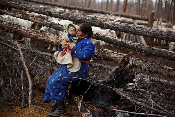 Женщина держит на руках своего внука.