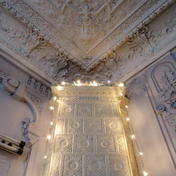 Камин с окрашенными глазурью изразцами под лепным потолком.