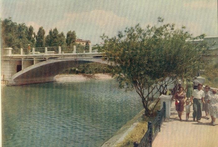 Одноарочный железобетонный мост, перекинутый через озеро.