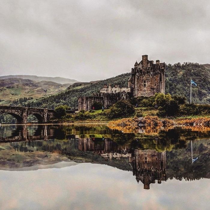 Огромный замок Эйлен-Донан, расположенный в Шотландии, Гвидо Гутьеррес Руис компактно «отразил» в луже, собравшейся на скале после дождя.