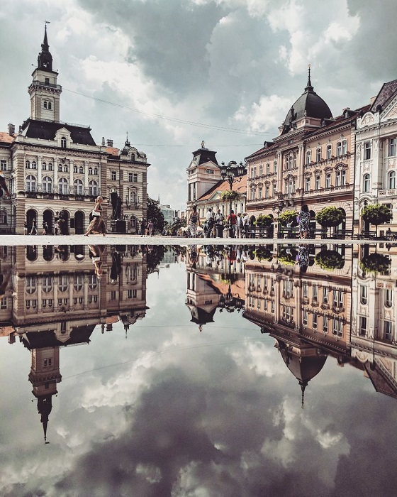 Хмурое небо над улицей в сербском городе Нови-Сад и его перевернутое отражение в луже.