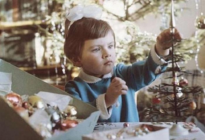 Девочка выбирает самые красивые игрушки для своей ёлки.