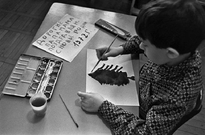 Мальчишка делает новогоднии открытки своими руками.
