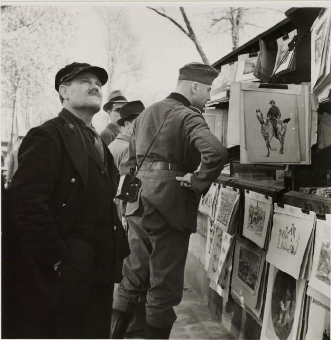 Немецкий солдат перед киоском на набережной Сены.
