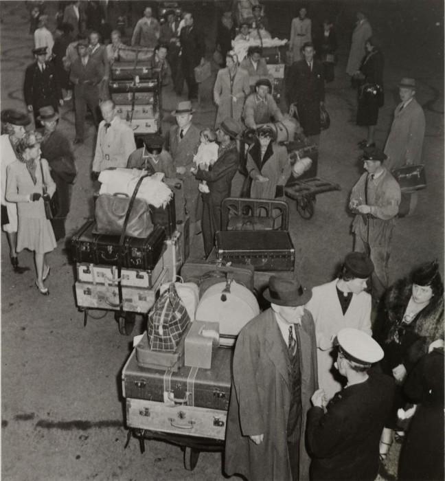 Пассажиры вокзала с огромной кучей чемоданов.