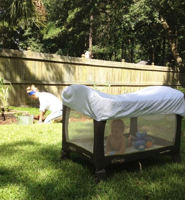 Манеж накрыт одеялом, для того, чтобы защитить ребенка от укусов комаров.