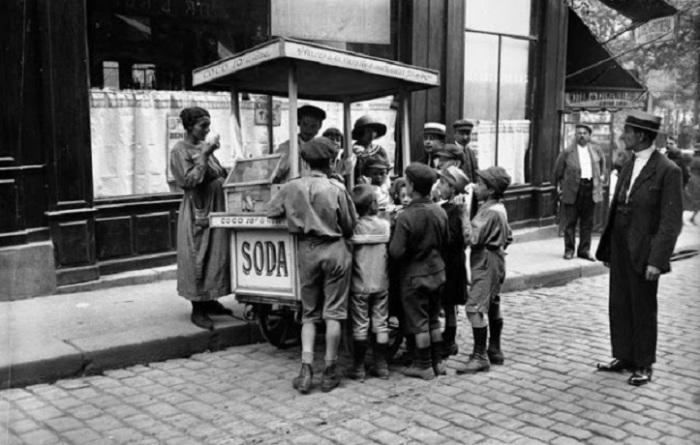 Продавец продает детям мороженое и напитки.