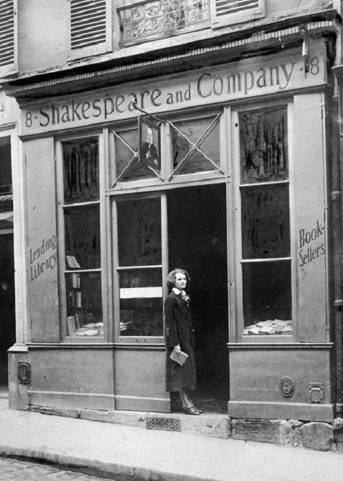 Женщина с книжкой в руках стоит возле магазина «Шекспир и Компания».