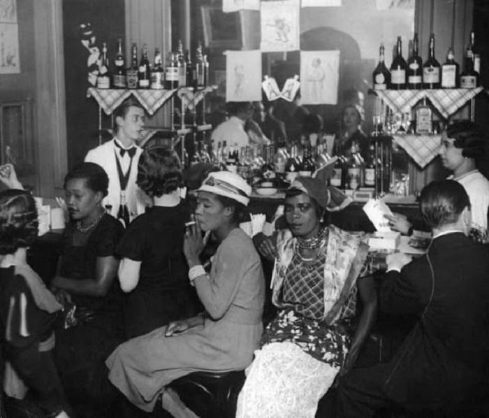 Женщины и мужчины возле барной стойки.