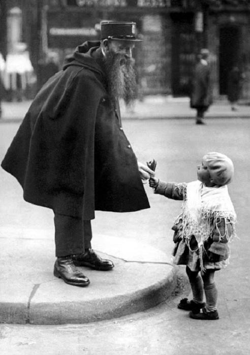 Маленький ребенок протягивает цветы работнику полиции.