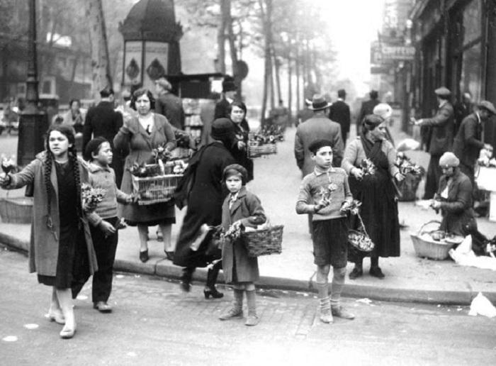 Взрослые и дети торгуют лилиями на улицах Парижа. 1930 год.