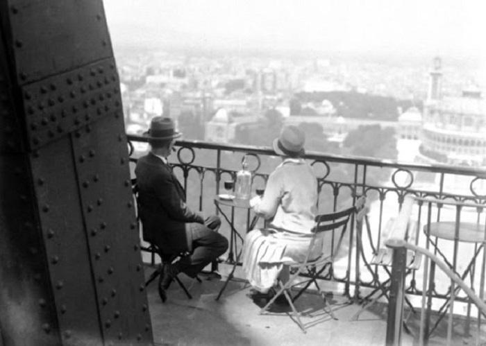Молодые люди сидят в ресторане на Эйфелевой башне.