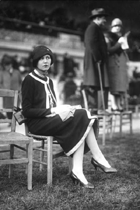 Женщина одета по моде 1920 годов.