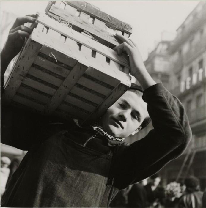 Юноша, несущий деревянный ящик на плече.