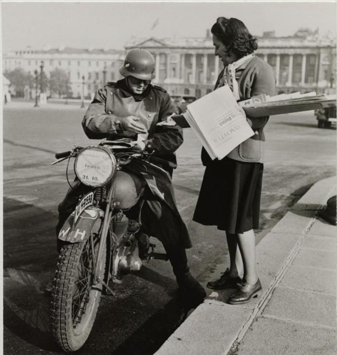 Немецкий солдат на своем мотоцикле покупает газету.