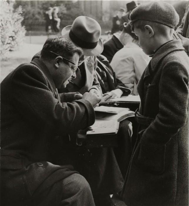 Мужчина очень внимательно рассматривает почтовую марку.