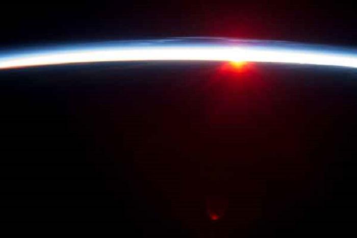 Тонкая линия земной атмосферы и заходящее Солнце.