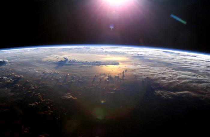 Горизонт Земли в момент, когда солнце садится над Тихим океаном.